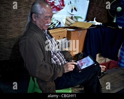 Ein alter asiatischer Mann mit einem iPad Tablet um zu spielen. S. E. Asien Thailand - Stockfoto
