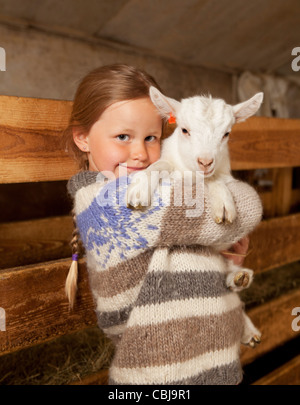 Mädchen Holidng Ziege Kind, Goat Farm Island - Stockfoto