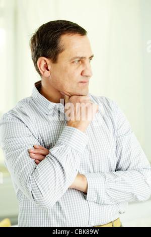 Porträt von reifer Mann mit verschränkten Armen sein Kinn berühren - Stockfoto