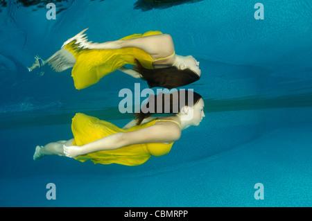 Frau schwimmt im Pool mit gelben Kleid - Stockfoto