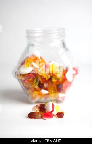 Eine Handvoll von Gelee-Süßwaren vor einem Glas voller Süßigkeiten platziert - Stockfoto
