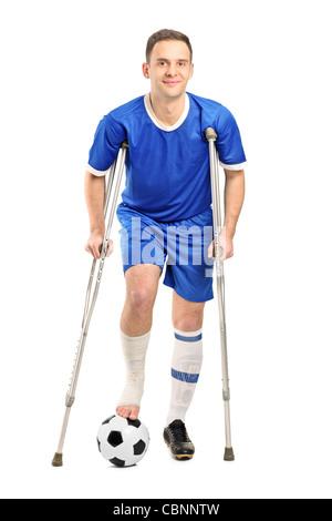 In voller Länge Portrait von einem verletzten Fußballspieler auf Krücken - Stockfoto
