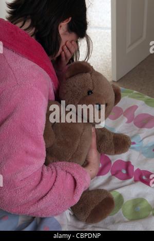 Über die Schulter Irl umklammert einen Teddybär sitzt auf ihrem Bett hand über die Augen Weinen. - Stockfoto