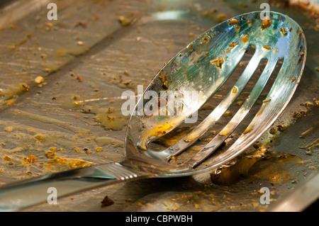 Eine fettige geschlitzte Löffel in einer Küche, die darauf warten, gespült werden. - Stockfoto