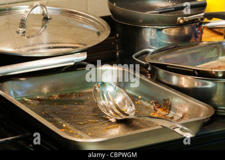Eine Auswahl der Röstung, Dosen, Töpfe und Pfannen in der Küche warten darauf, gespült werden. - Stockfoto