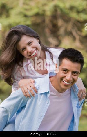 Hispanic Mann geben Frau Huckepack Fahrt - Stockfoto