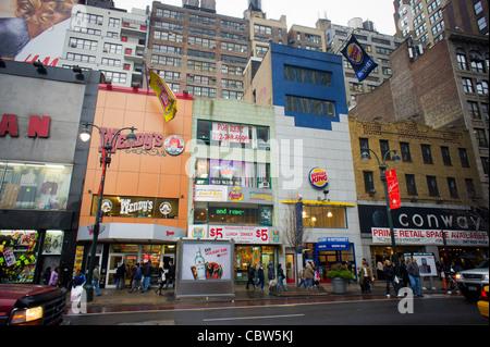 Wendys und Burger King Fastfood-Restaurants sind fast nebeneinander auf der West 34th Street in New York - Stockfoto