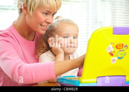 Mutter lehrt Tochter zu benutzen elektronische Spiel / Spielzeug - Stockfoto