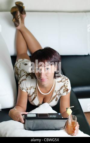 eine junge Frau auf einem Sofa liegend, auf einem Notebook arbeitet und einen Saft zu trinken - Stockfoto