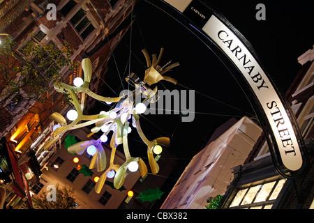 Weihnachtsbeleuchtung und Dekorationen geschmückt wie Holly und Mistel in der Carnaby Street in London - Stockfoto