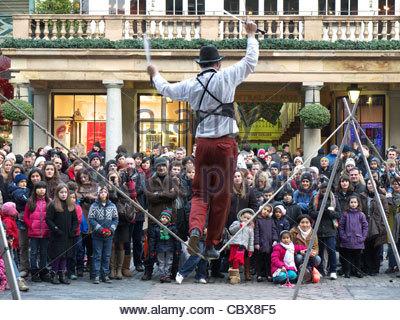 Ein Seiltänzer unterhaltsam eine Menge von Touristen in Covent Garden London UK - Stockfoto