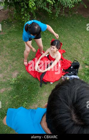 Peking, Chaoyang Park. Blick auf Braut und Make-up-Künstler, Vorbereitung für ein Fotoshooting Hochzeit Fotograf. - Stockfoto