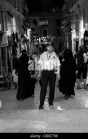 Basar, Istanbul. Security Guard und zwei verschleierte Frauen auf der Straße. - Stockfoto