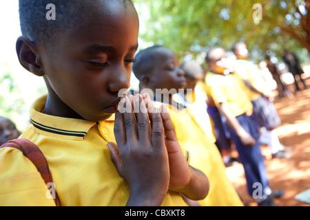 Studenten beten während Schulversammlung in Morogoro, Tansania, Ostafrika. - Stockfoto