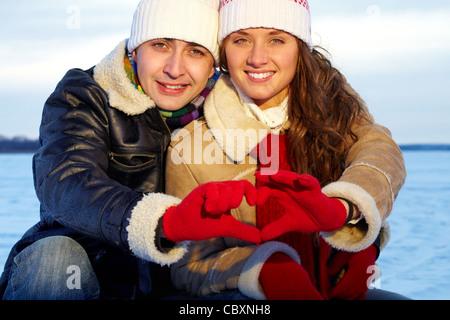 Porträt des glücklichen Paares in warme Kleidung, Hände, Herz indem - Stockfoto