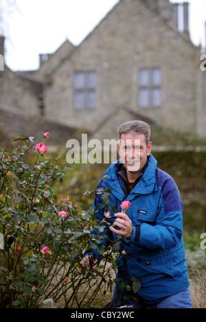 Chris Clennet der Garten Manager von Wakehurst Place in Sussex mit einem Eve Price stieg im Dezember noch in voller - Stockfoto
