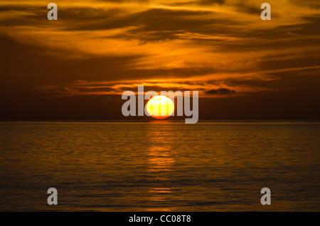 Zuerst berührt die Sonne den Horizont, schaffen einen schönen goldenen Schimmer auf dem Wasser und die leichten, - Stockfoto