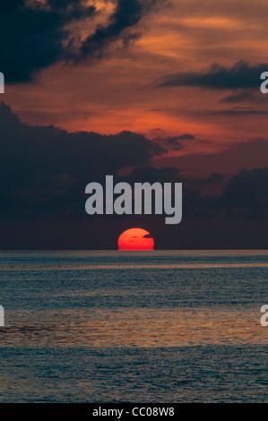 Die Sonne ist teilweise unter dem Horizont, mit dem ruhigen Wasser des Pazifischen Ozeans in der Unterseite des - Stockfoto