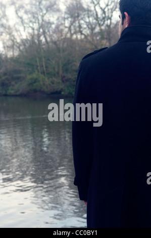 Rückansicht eines jungen Mannes im Wintermantel am Fluss - Stockfoto