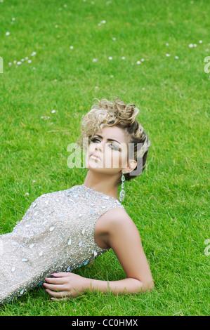 Ernste junge Frau liegend auf dem Rasen wegschauen - Stockfoto