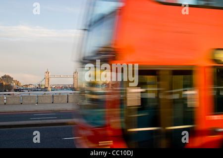 Einem roten Londoner Bus Reisen über London Bridge in der Tageszeit mit Tower Bridge im Hintergrund - Stockfoto