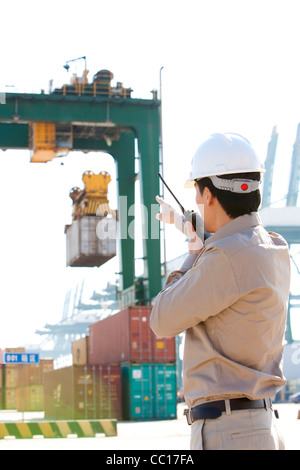 Versand Industrie Arbeiter Regie Krane mit seinem walkie-talkie - Stockfoto