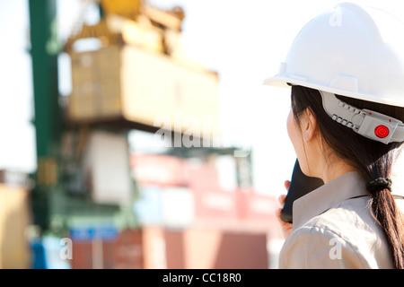 Versand Industrie Arbeiter Regie Krane mit ihr walkie-talkie - Stockfoto