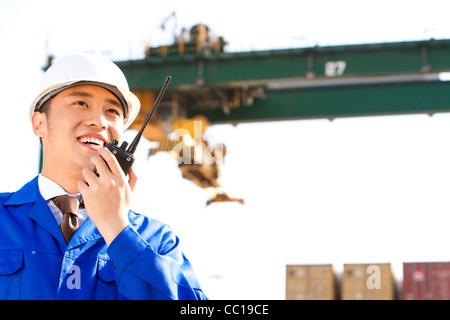 Versand Industriemanager Regie Krane mit seinem walkie-talkie - Stockfoto