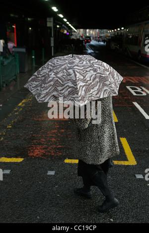 Frau mit Regenschirm geht in Glasgow Schottland - Stockfoto