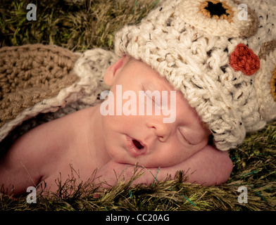 Neugeborene Mädchen schläft auf einer pelzigen grüne Decke, die wie Rasen aussieht hat sie auf einem Strick Eule - Stockfoto