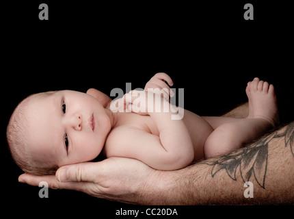Neugeborenes Baby junge von seinem Vater liebevoll gehalten. - Stockfoto