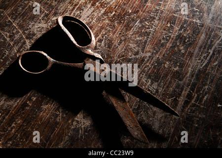 Rostige Schere auf alte, zerkratzte, hölzerne Tischplatte - Stockfoto