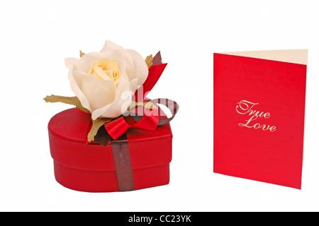 Herz Form rot Pralinenschachtel mit Rose und eine rote Karte isoliert auf weißem Hintergrund - Stockfoto