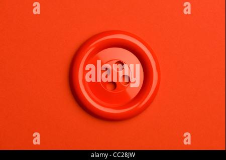 Ein roter Knopf auf rotem Grund - Stockfoto