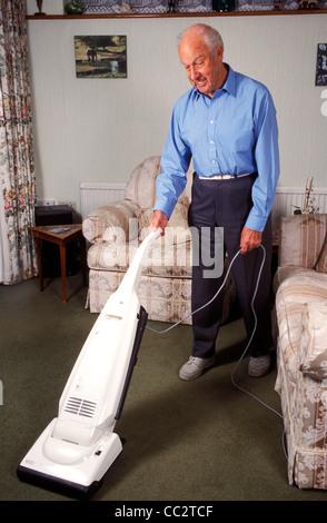 reifer Mann Teppich saugen - Stockfoto