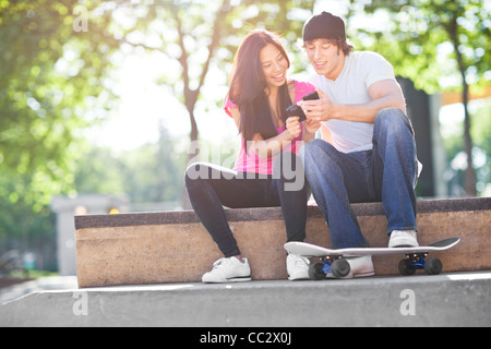 USA, Washington, Seattle, multi-ethnischen Pärchen sitzen mit Skateboard, mit Handy - Stockfoto