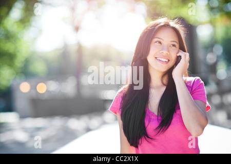 USA, Washington, Seattle, junge Chinesin, die mit Handy im freien - Stockfoto