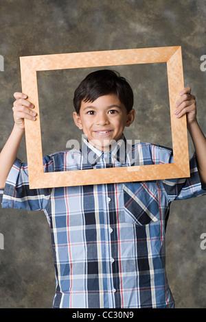 Porträt von lächelnden jungen (8-9) auf der Suche durch Rahmen, Studio gedreht - Stockfoto