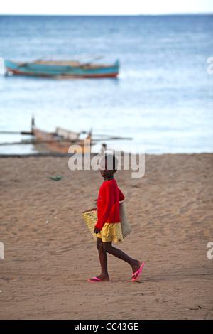 Eine madagassische Mädchen tragen rosa Flip-Flops und eine Vime Korb zu Fuß am Strand in Nosy Komba, Madagaskar - Stockfoto