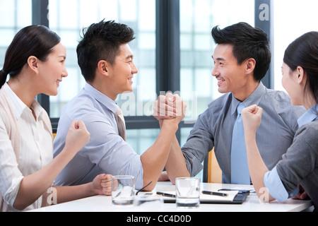 Unternehmer-Armdrücken mit Kollegen jubeln sie auf - Stockfoto