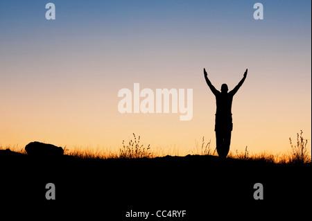 Mann mit erhobenen Armen in der indischen Landschaft in der Dämmerung. Silhouette - Stockfoto