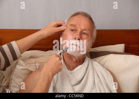 Ein Bedbound Mann in seiner 60 ist durch seine Frau/Pfleger rasiert wird - Stockfoto