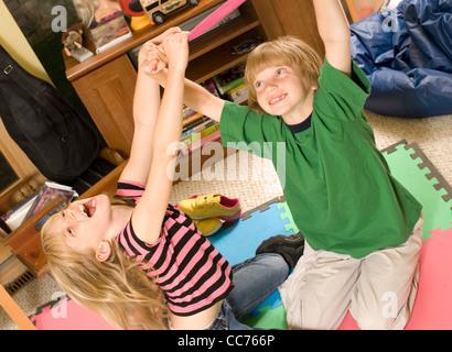 Zwillinge, Ringen und kitzeln in ihrem Spielzimmer - Stockfoto
