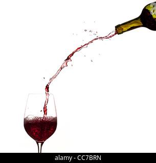 Rotwein wird direkt aus der Flasche in ein Glas gegossen - Stockfoto
