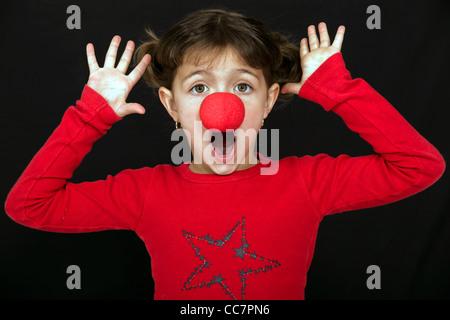 Kleines Mädchen überrascht mit einer Clownsnase - Stockfoto