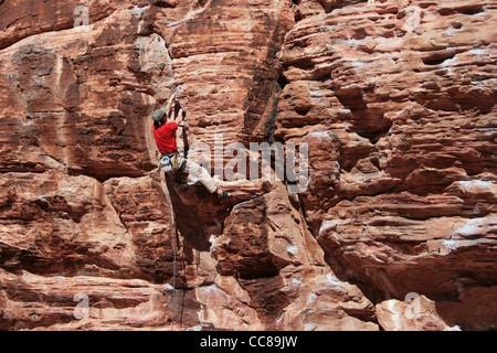 Kletterer Klettern eine aus rotem Sandstein-Klippe bei Red Rocks, Nevada rot - Stockfoto