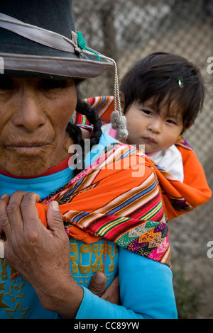Eine Frau trägt ein Baby auf dem Rücken in einem Armenviertel von Lima, Peru, Südamerika. - Stockfoto