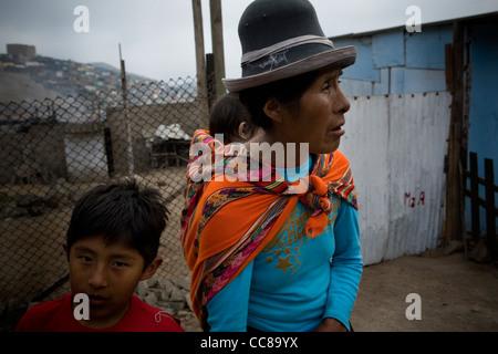 Eine Familie steht vor ihrer kleinen Hütte in Lima, Peru, Südamerika. - Stockfoto