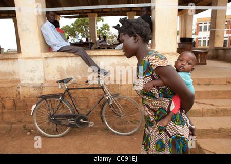 Eine Mutter trägt ihr Kind, ein Gesundheitszentrum in Kumi, Uganda, Ostafrika. - Stockfoto
