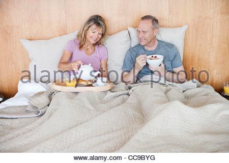 Älteres Paar im Bett zu frühstücken - Stockfoto